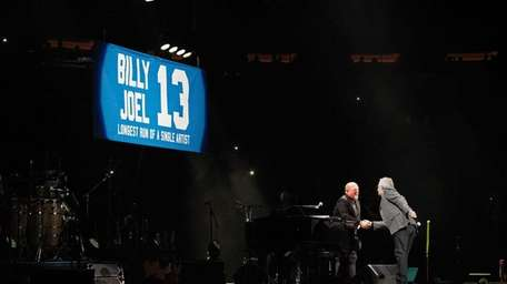 Billy Joel, left, takes the stage at Madison