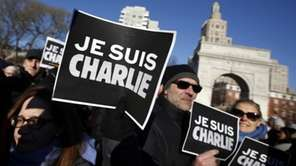 "Attendees hold ""Je Suis Charlie"" (I am Charlie)"