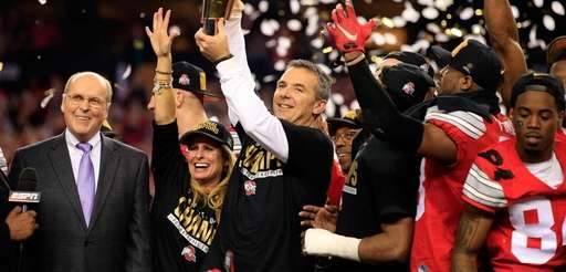 Ohio State head coach Urban Meyer hoists the