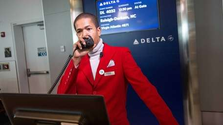 A gate agent calls for the boarding of