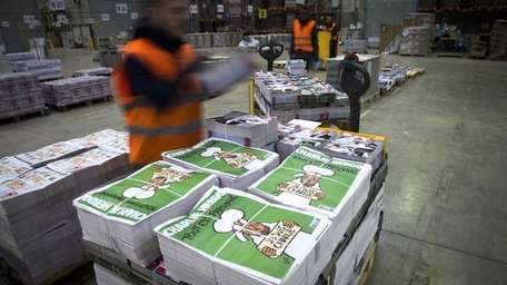 Employees check the arrival of the forthcoming edition