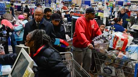 Shoppers pay for their items and walk with