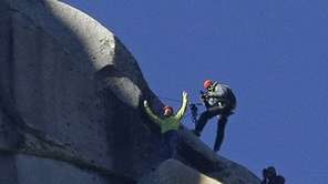 Tommy Caldwell, top, raises his arms after reaching