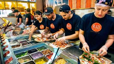 Pizza is an assembly-line production at Blaze Pizza.