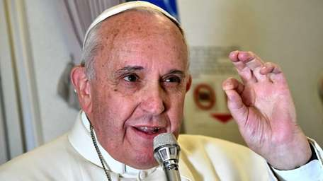 Pope Francis addresses journalists sitting on board a