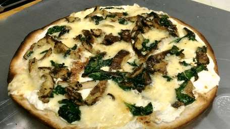 A white pizza with mushrooms, spinach, fontina cheese