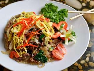 Japchae, clear sweet potato noodles, are stir-fried with