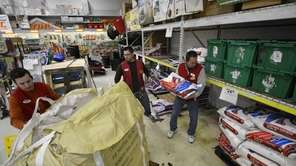Workers at Ace Hardware in Bellmore stock shelves