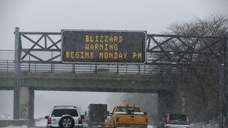 Southbound traffic moves past a blizzard warning sign