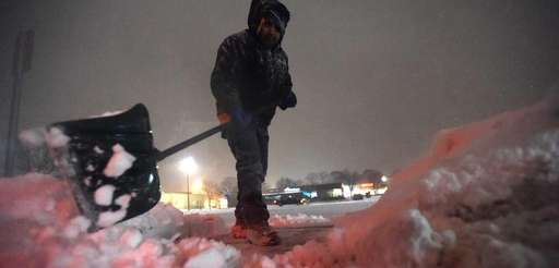 Lucao Gonzalez shovels snow in the Centereach Mall