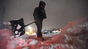 Lucao Gonzalez shovels snow in the Centereach Mall