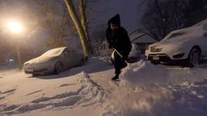 Anthony Ilvento works to clear snow from in