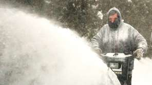 Bob Bartek uses a snow blower to clear