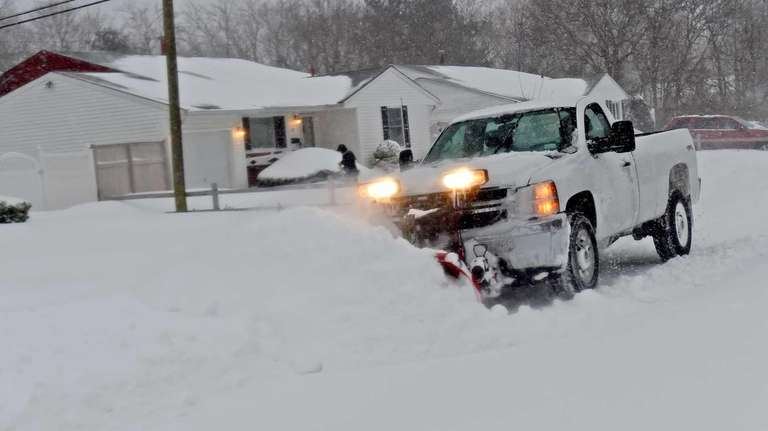 A snow plow works to clear snow from