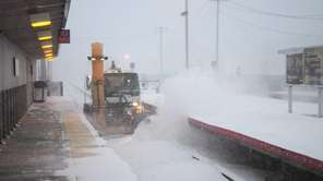 Snow removal equipment blows snow from the tracks