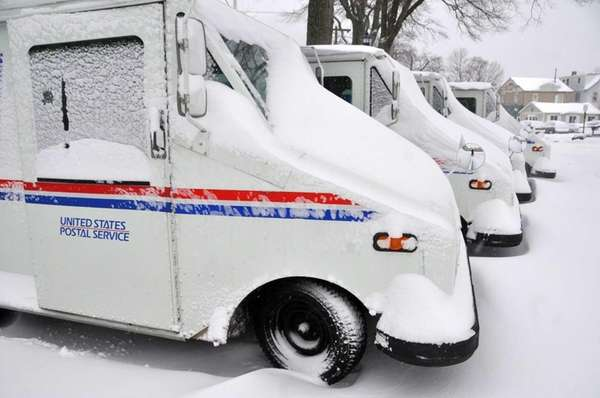 Snow-covered United States Post Office delivery vehicles parked
