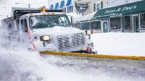 A snowplow travels down Front Street in Greenport