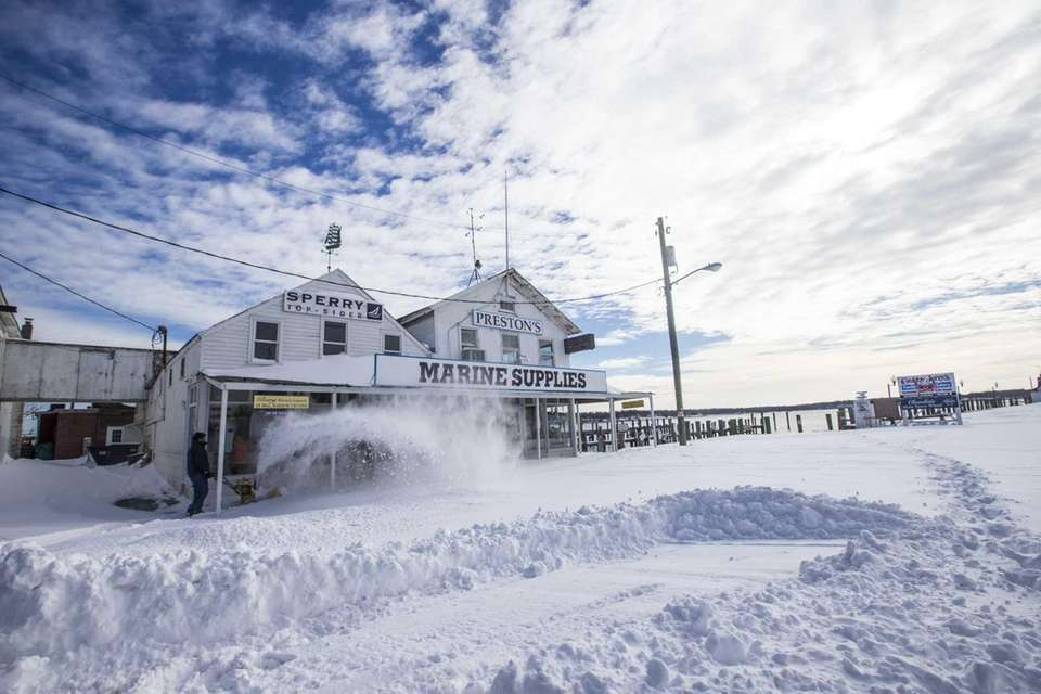 A snowblower clears snow on Main Street in