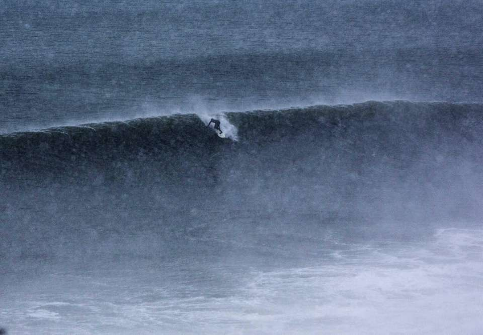 A surfer rides a wave at Turtle Cove
