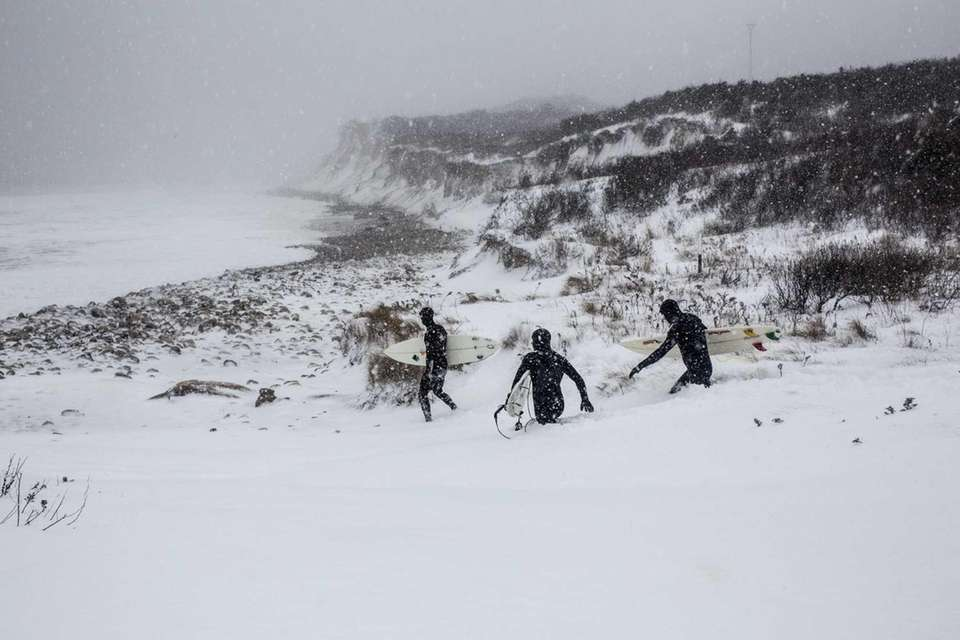 Surfers head to the ocean through the snow