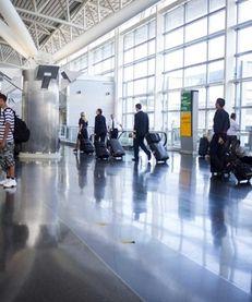 People walk in the American Airlines/US Airways Terminal