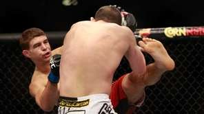 Al Iaquinta, left, kicks at Joe Lauzon in