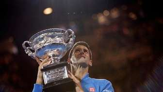Novak Djokovic poses with the trophy after defeating