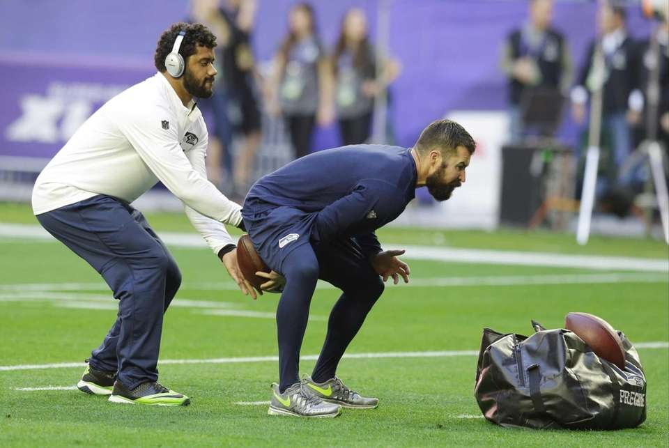 Seattle Seahawks quarterback Russell Wilson, left, warms up