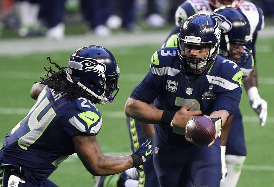 Russell Wilson hands the ball to Marshawn Lynch