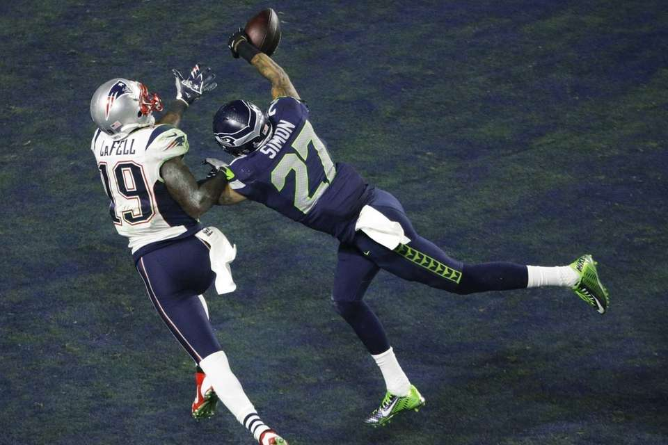 Seattle Seahawks cornerback Tharold Simon breaks up a