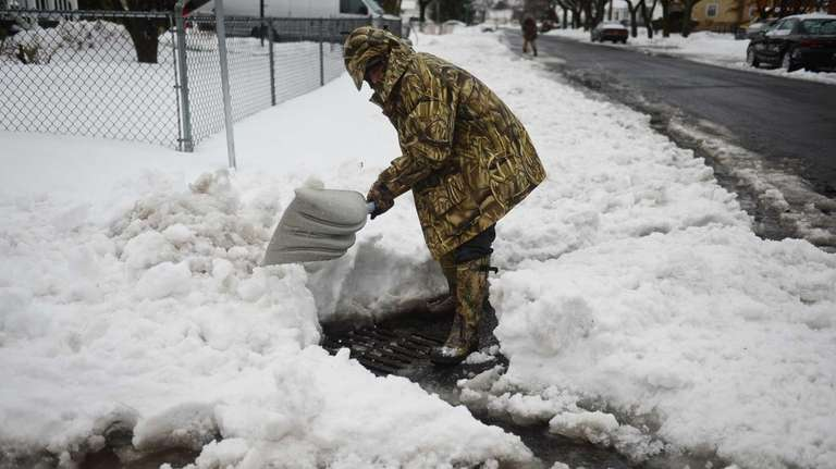 Moses Morales clears a clogged storm drain of