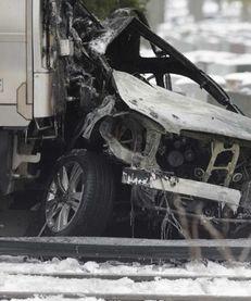 Investigators examine the charred front car of a