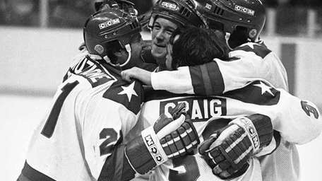 Mike Eruzione, left, is hugged by teammates John