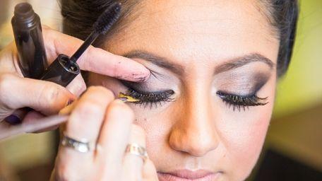 Makeup artist Anna Naso applies eyelashes to model