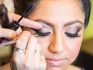Makeup artist Anna Naso applies eyelashes to model