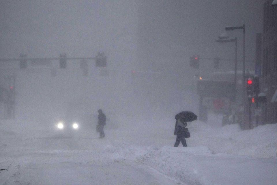 Pedestrians cross Kneeland Street in Boston, Mass. during