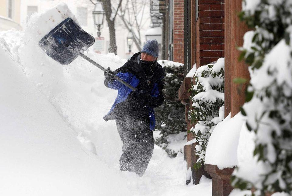 Judith Hanson shovels snow on Beacon Hill in