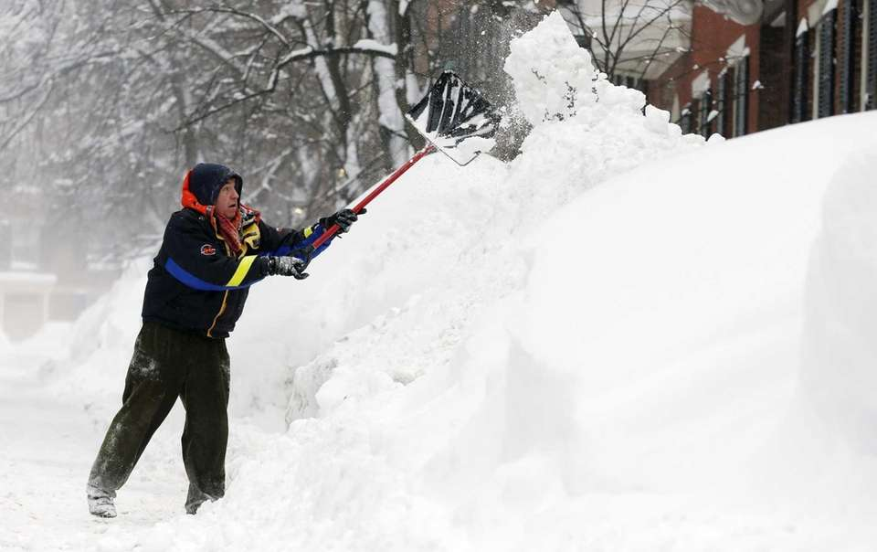 Brian Vallely shovels snow on Beacon Hill in