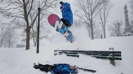 A snowboarder jumps over a friend and a
