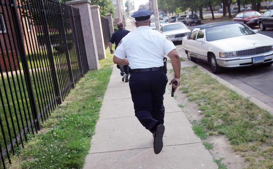 Police officers with guns drawn run toward the