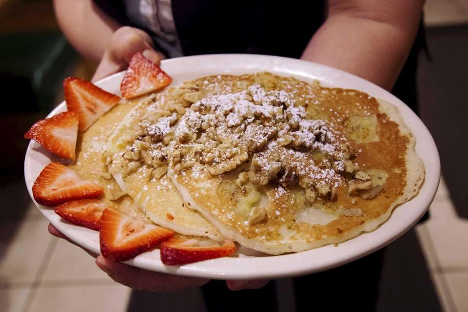 A late-night order of pancakes topped with strawberries,
