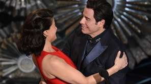 John Travolta and Idina Menzel embrace before presenting