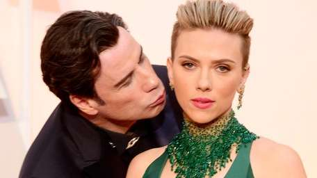 John Travolta kisses Scarlett Johansson on the red