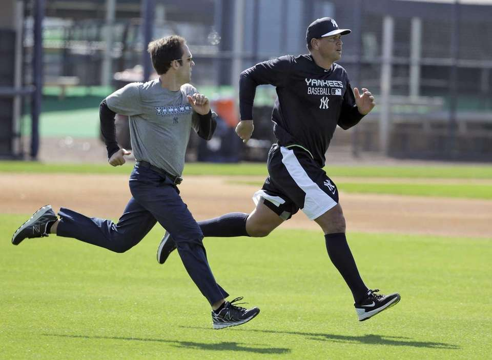 Alex Rodriguez, right, runs with a trainer while