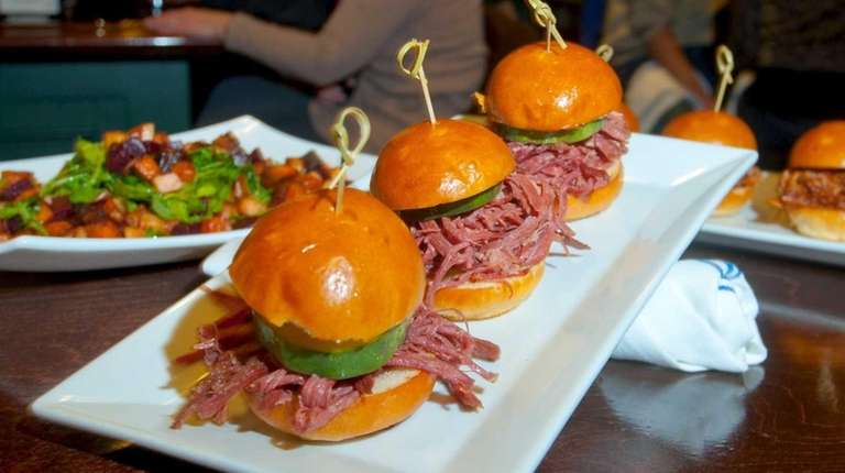 Corned beef sliders with pickles are served at