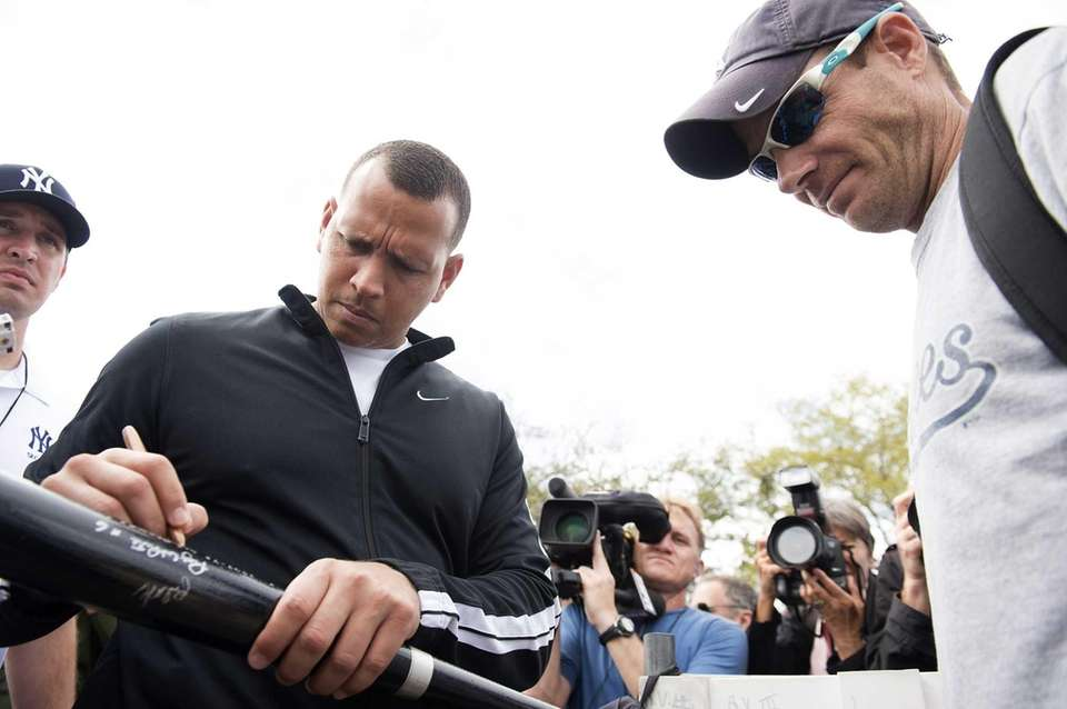 The Yankees' Alex Rodriguez signs autographs for fans