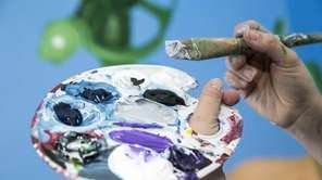 Artist Melissa Digiose paints a mural with an